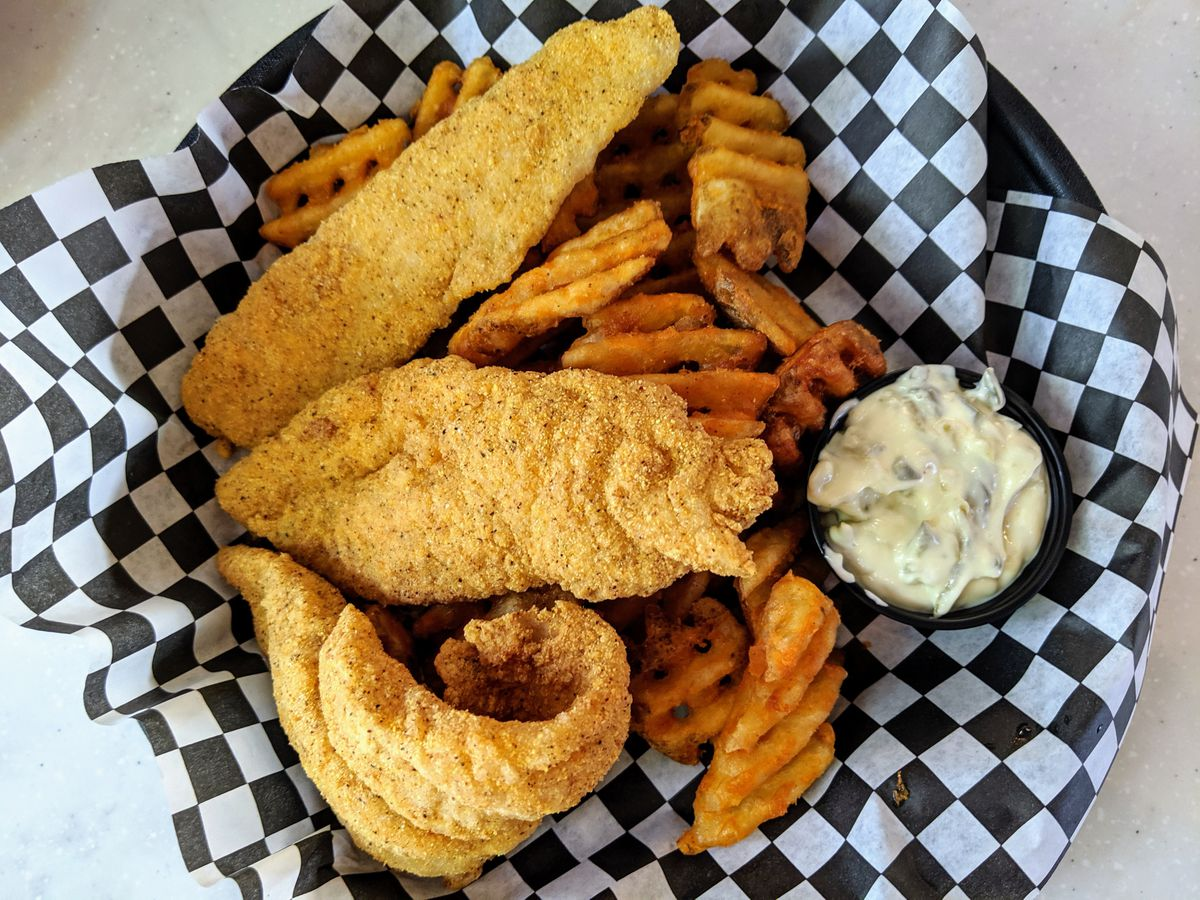 Fried fish with waffles fries under checkered paper basket on a white table.