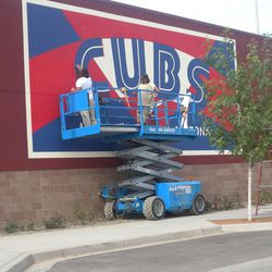 Putting finishing touches on another sign at Cubs Park