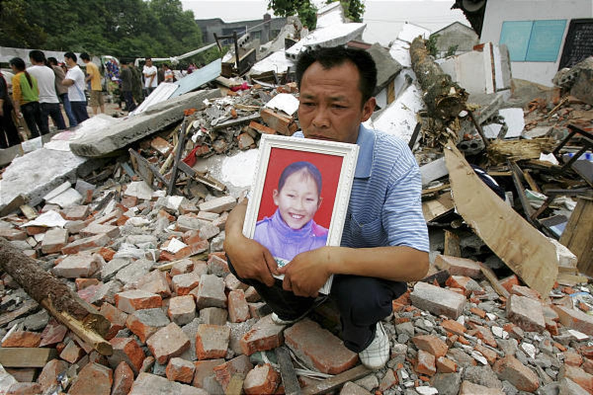 In this May 2008 file photo, a father holds a photo of his daughter who was killed in an earthquake, while sitting in the ruins of the Fuxin No. 2 Primary School in Wufu, in China's southwest Sichuan province.