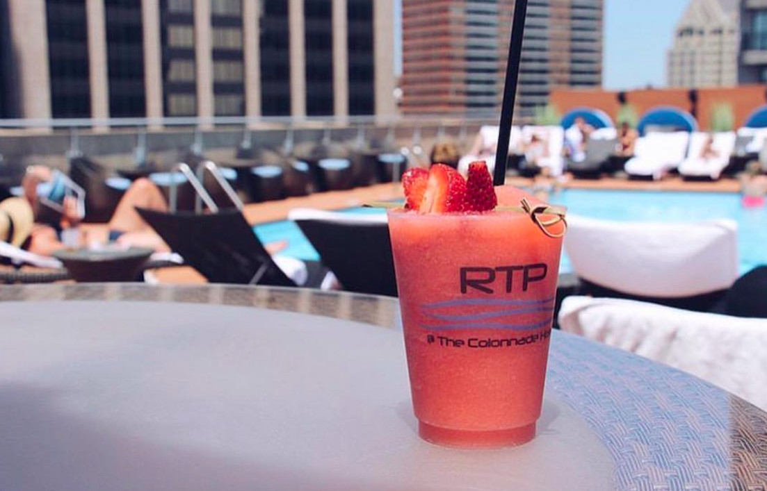 A frosé garnished with strawberries and served in a Colonnade Hotel branded glass is sitting on a table in front of a pool