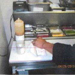 An employee uses a dry clothe to clean a cutting board.