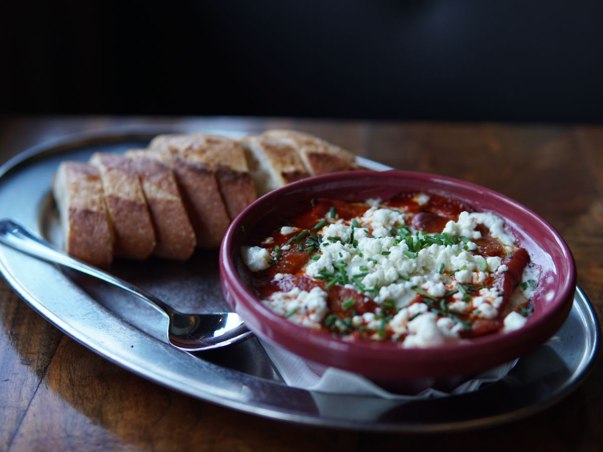 A purple bowl of feta-covered tomatoes sits on an oval of a white plate, with a bunch of sliced baguette