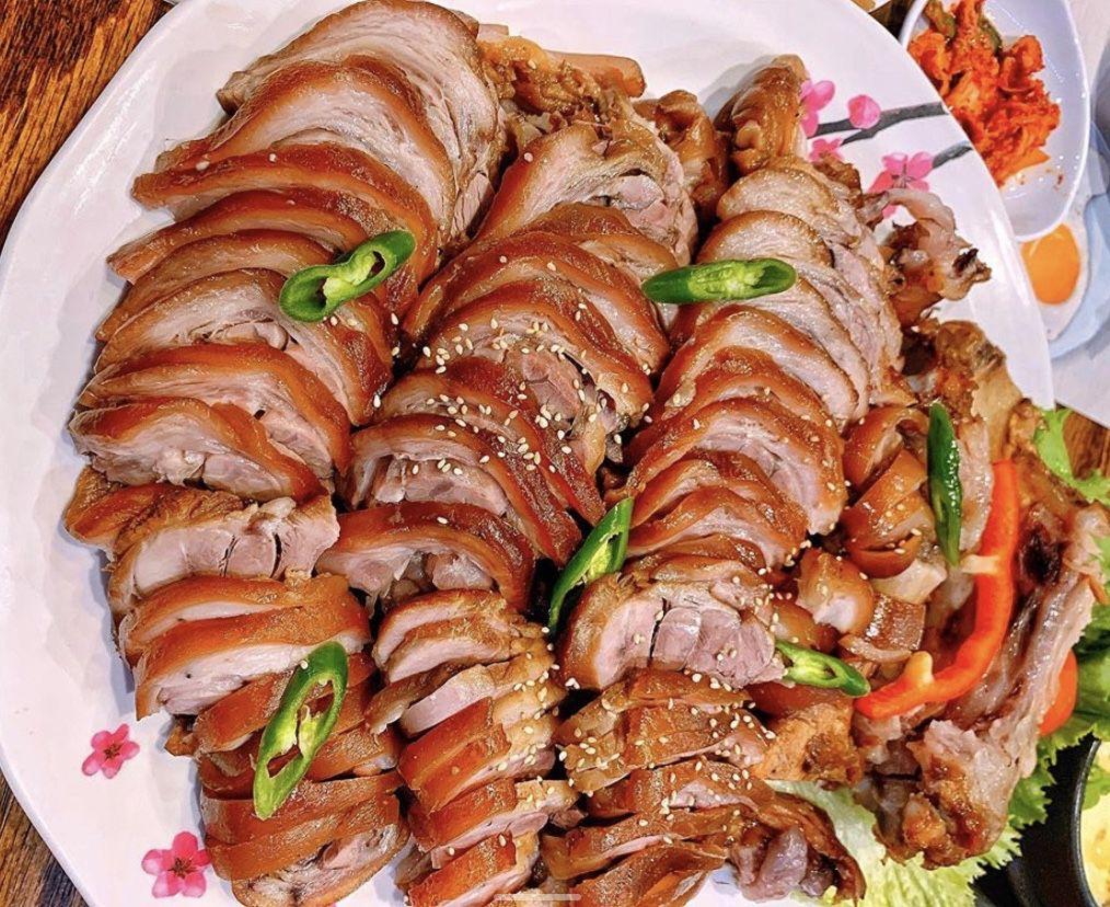 Many slices of skin-on pork laid on a white platter