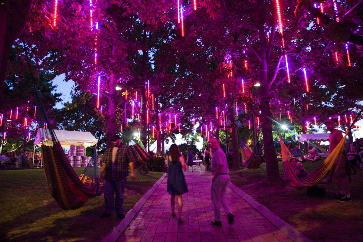 The Spruce Street Harbor Park in Philadelphia. There are hammocks and many lights hanging from trees. It is night.