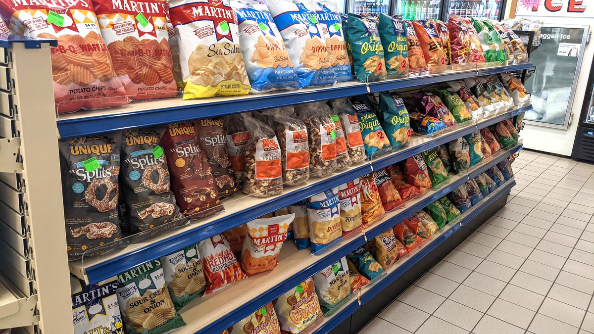 A potato chip aisle inside a convenience store with several different bagged varieties.