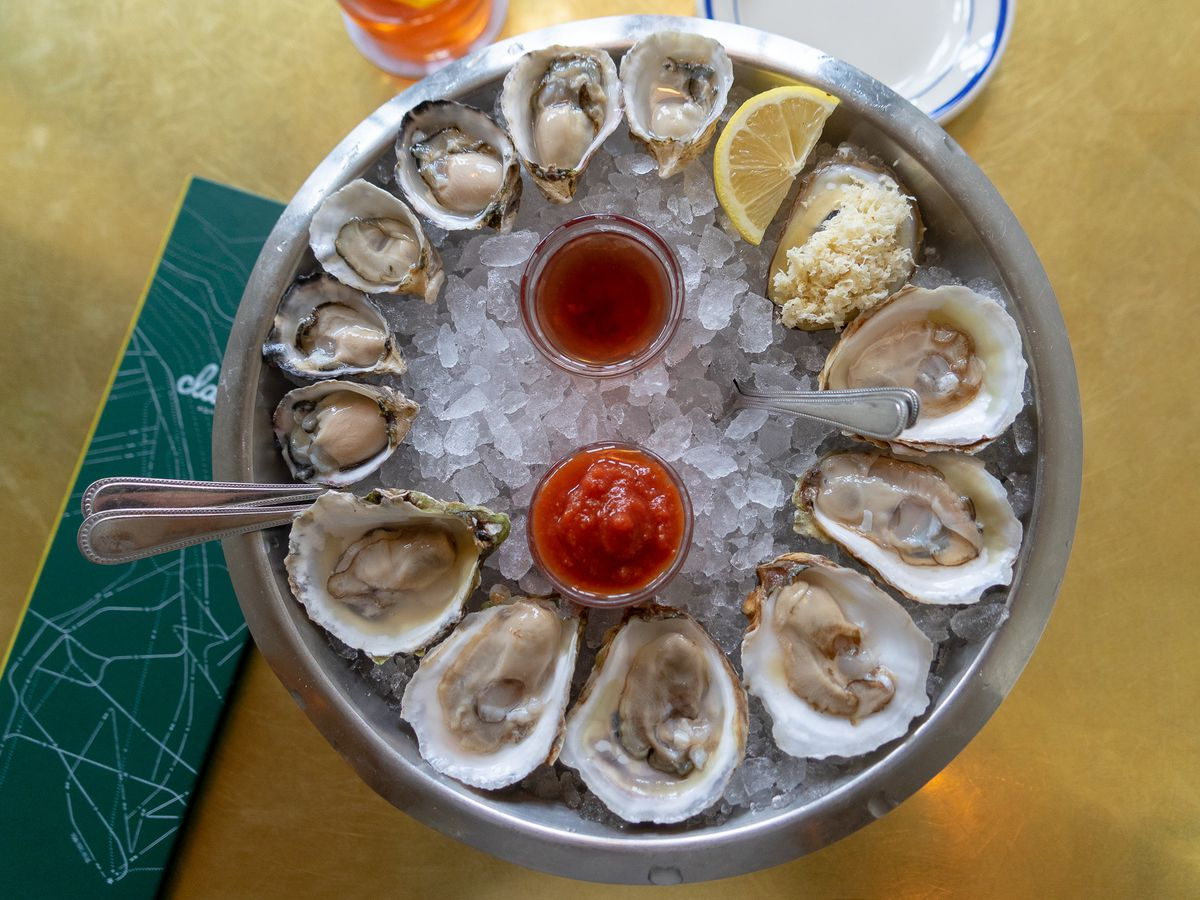 From above, oysters arranged around a circular bed of ice with a set of spoons, slice of lemon, and two dipping sauces