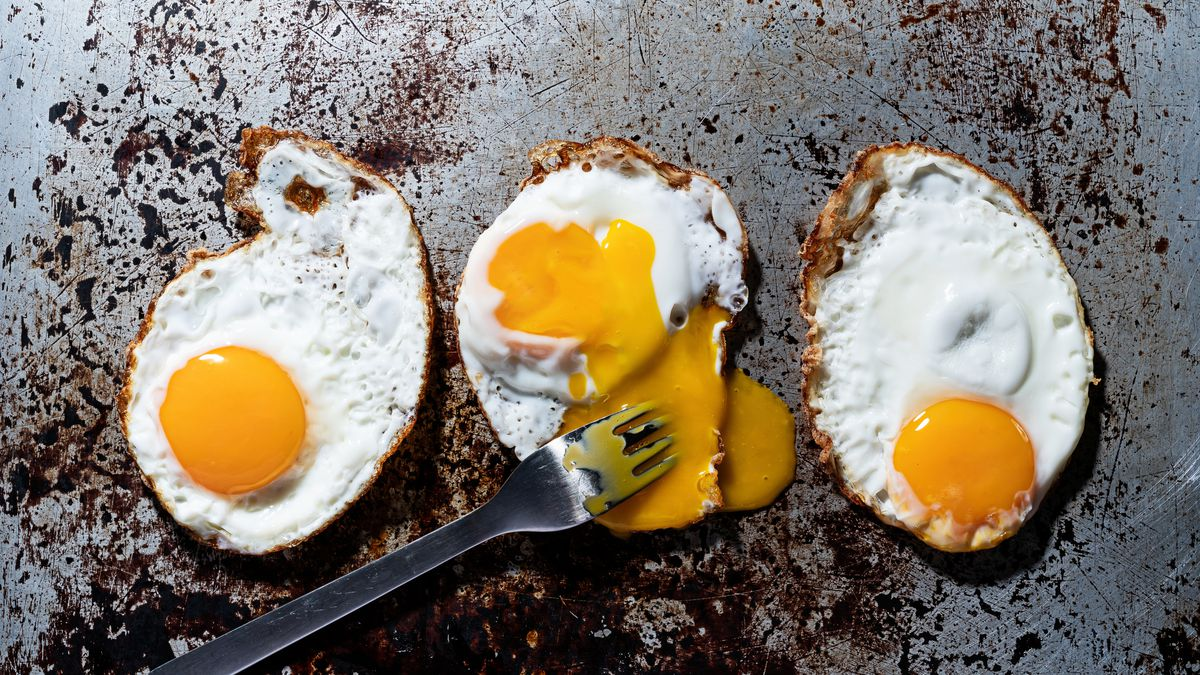 Photo of fried eggs with a fork.