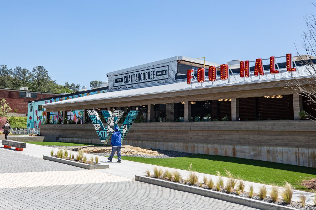 """The outside entrance to Chattahoochee Food Works in northwest Atlanta on clear blue sunny day. Big red sign with the words """"Food Hall"""" sits above the wood covered patio while a may in a ball cap and blue windbreakers walks past a small strip of bright green grass on the newly paved sidewalk"""