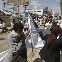 Protesters run from tear gas released by riot police during clashes near the U.S. Embassy in Sanaa, Yemen, Friday, Sept. 14, 2012, as part of widespread anger across the Muslim world about a film ridiculing Islam's Prophet Muhammad.