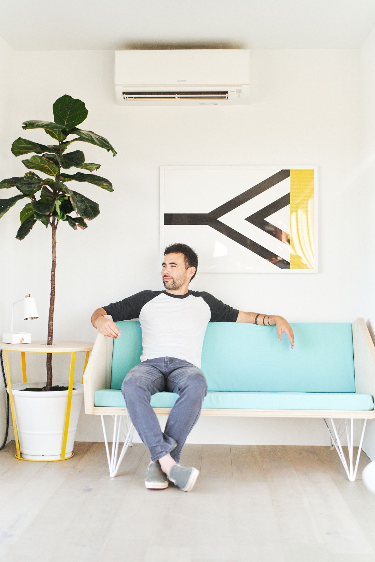 A photo of a man, Ben Uyeda, sitting on a DIY turquoise and white couch with a yellow tree coffee table on his left.