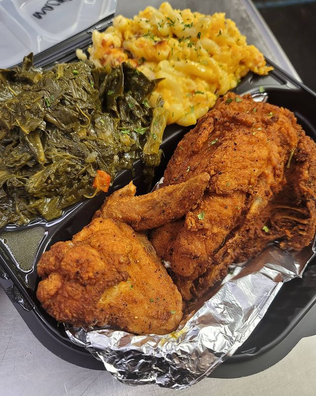 A container of fried chicken, collard greens, and mac and cheese.
