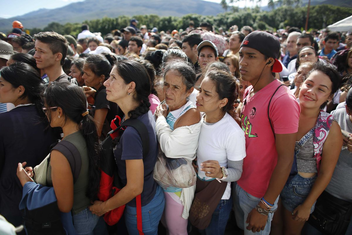 FILE - In this July 17, 2016 file photo, Venezuelans wait in line to cross into Colombia through the Simon Bolivar bridge in San Antonio del Tachira, Venezuela. The United Nations says an estimated 2.3 million Venezuelans had fled the country as of June 2