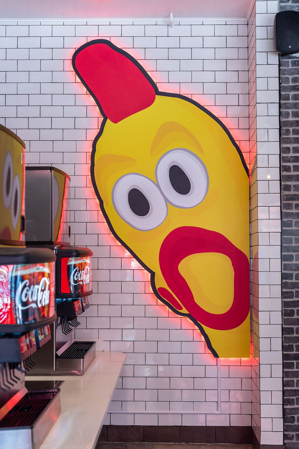 A neon-backed image of a rubber chicken peeks out from a wall inside a restaurant.