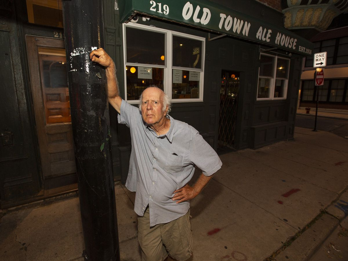A character leaning on a light pole in front of a bar.