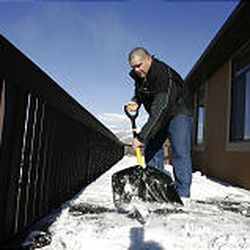 Rulon Gardner scrapes ice and snow from the deck of his North Salt Lake home. He moved to the area to be close to Salt Lake International Airport. He travels 200 to 300 days a year.