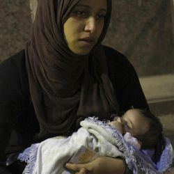 """In this Friday Sept. 14, 2012 photo, the wife of Ismail Rashad, 36, holds their 25-day-old daughter, named Ganna, or """"Heaven"""" as they wait outside the Zenhoum morgue for authorities to release his body in Cairo, Egypt. His family and doctors at a Cairo hospital said Rashad  died yesterday from wounds from rubber bullets In clashes Friday that brought the first Egyptian to be killed in Tahrir Square protests since Islamist President Mohammed Morsi was elected and took office this summer."""