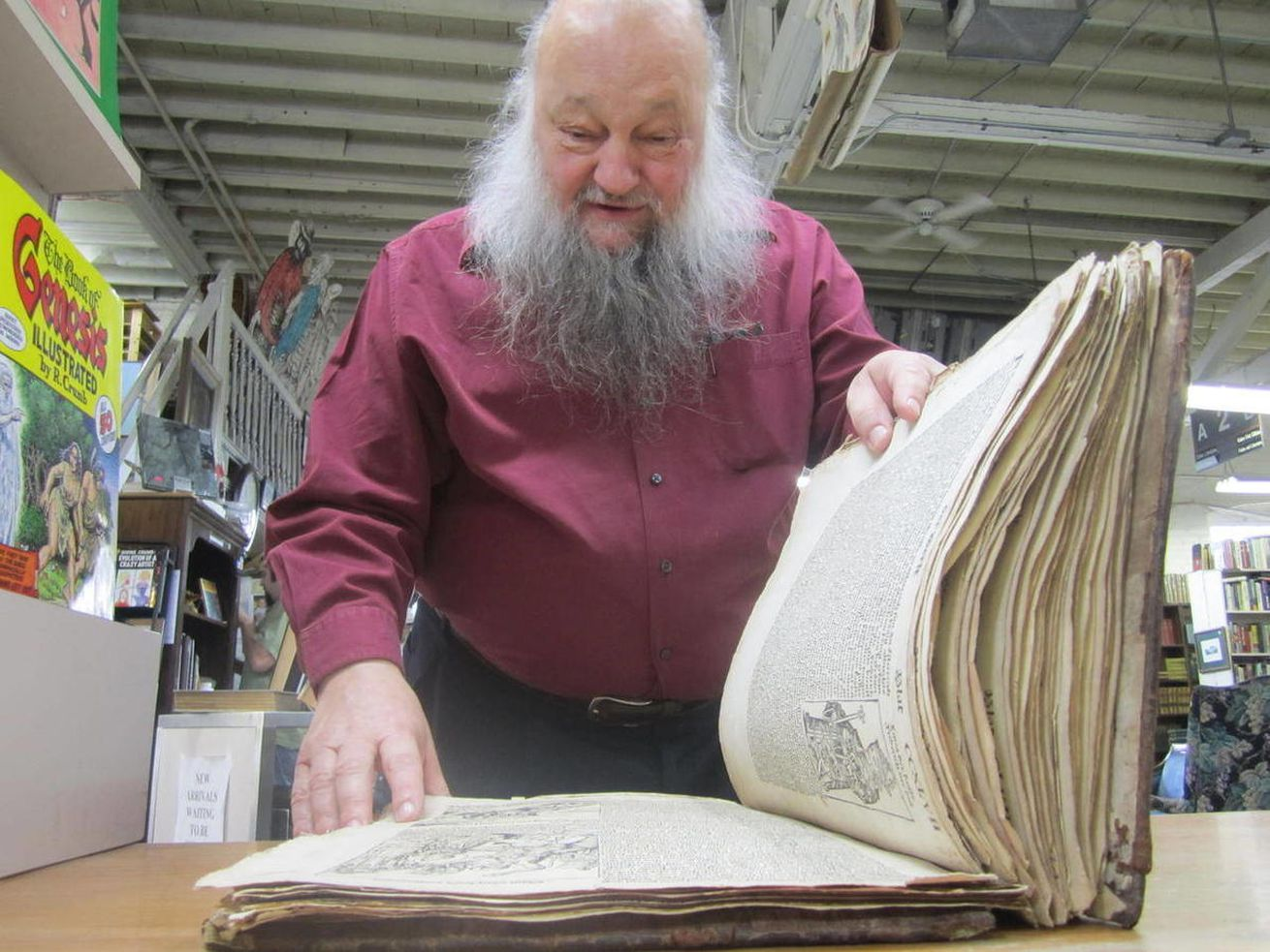 In this photo taken Saturday, April 23, 2011, Utah book dealer Ken Sanders looks over a copy of the Nuremberg Chronicle published in 1493. The book is on display at Ken Sanders Rare Books in Salt Lake City. Sanders across the 500-year-old German language