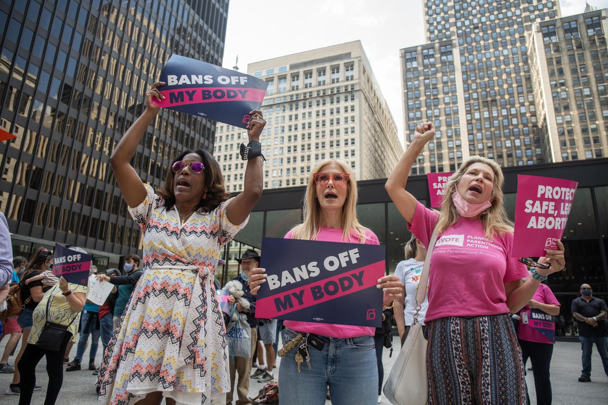 """(From left) Cook County Board Commissioner Donna Miller, Stacy Michelon and Laura Tucker chant during the """"Bans Off My Body"""" rally, decrying Texas' new law that bans most abortions after six weeks into pregnancy, Friday afternoon at Federal Plaza in the Loop."""