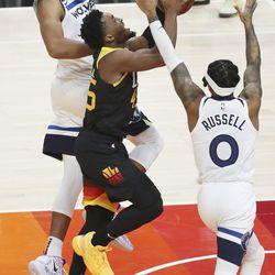 Utah Jazz guard Donovan Mitchell (45) is heavily defended by Minnesota Timberwolves center Karl-Anthony Towns (32) and Minnesota Timberwolves guard Ashton Hagans (0) in Salt Lake City on Saturday, Dec. 26, 2020.