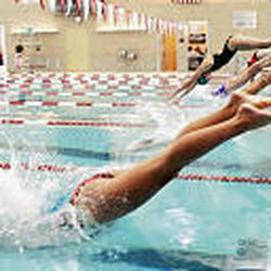 Members of high school girls swim teams make a splash as they dive into the Park Center pool during the early November meet.