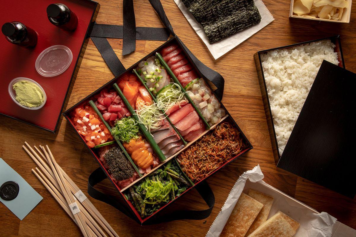 A box of sushi next to rice, nori seaweed and chopsticks