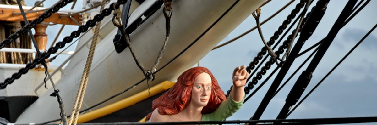 A sculpture of a woman with red hair on the bow of a boat