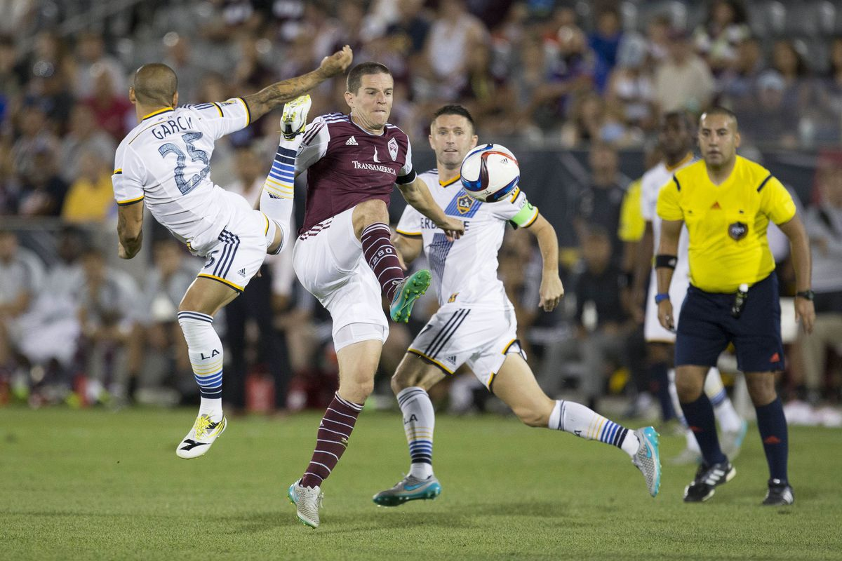 Captain Sam Cronin trying to work the ball against two Galaxy players