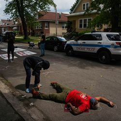 Lanessa Young, 18, draws around Haroon Garel's, 40, body during a teach in outside Chicago Board of Education President Miguel del Valle's home in Belmont Cragin to demand an end to police presence in schools, Wednesday afternoon, June 24, 2020. The Chicago Board of Education is set to decide whether to end Chicago Public Schools' $33 million contract with the Chicago Police Department and pull out police officers from schools.