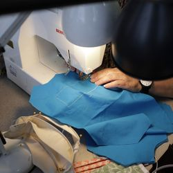 San Diego Opera costume director Ingrid Helton sews one of her masks with a window in San Diego.