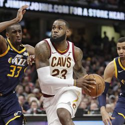 Cleveland Cavaliers' LeBron James, center, drives between Utah Jazz's Ekpe Udoh, left, and Thabo Sefolosha, from Switzerland, in the second half of an NBA basketball game, Saturday, Dec. 16, 2017, in Cleveland. (AP Photo/Tony Dejak)