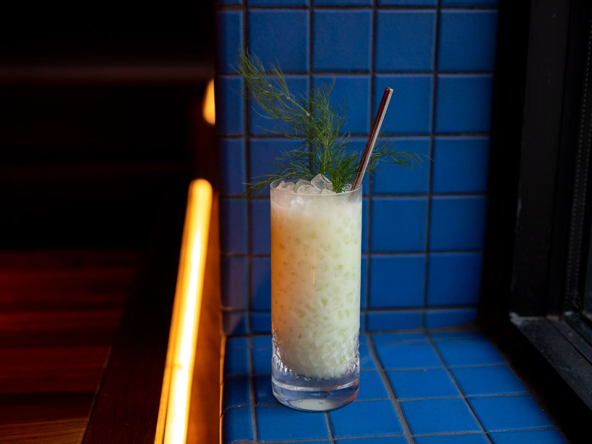 The cocktail is milky white with lots of crushed ice in a tall glass with a sprig of fennel on top.