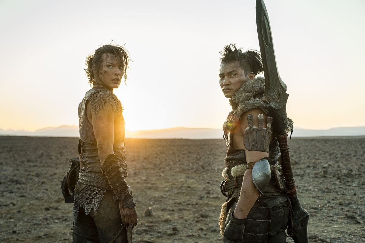Milla Jovovich with her Monster Hunter costar Tony Jaa looking at camera while the sun sets