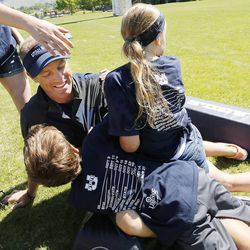Utah State University football coach Matt Wells gets tackled by his children Jadyn, Ella and Wyatt during a break in a kids football camp in Logan Friday, June 12, 2015.