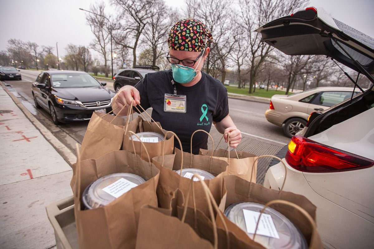 An employee at Mount Sinai Hospital unpacks a car of donated food from Mott St.