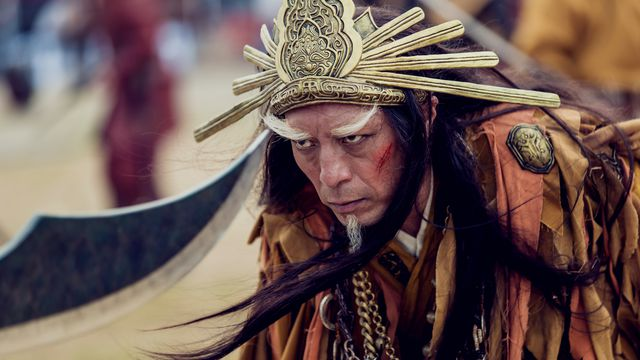 A sullen-looking older warrior with a huge starburst helmet and giant white eyebrows stares into the point of a blade in Netflix's Dynasty Warriors