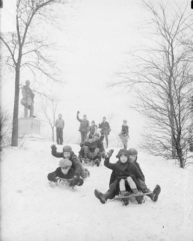 Image of children waving as they are sledding down a hill inChicago,Illinois. Three sleds with two children apiece are heading down the hill toward the camera. At the top of the hill four people are standing, one with a sled. To the left of th