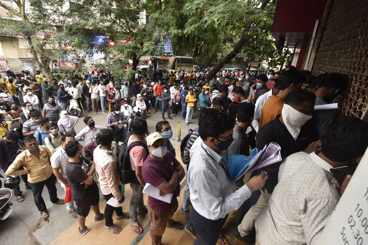 In this April 8, 2021 file photo, people wait in queues outside the office of the Chemists Association to demand necessary supply of the anti-viral drug Remdesivir, in Pune, India. As India faces a devastating surge of new coronavirus infections overwhelming the health care system, people are turning to desperate measures to keep loved ones alive.