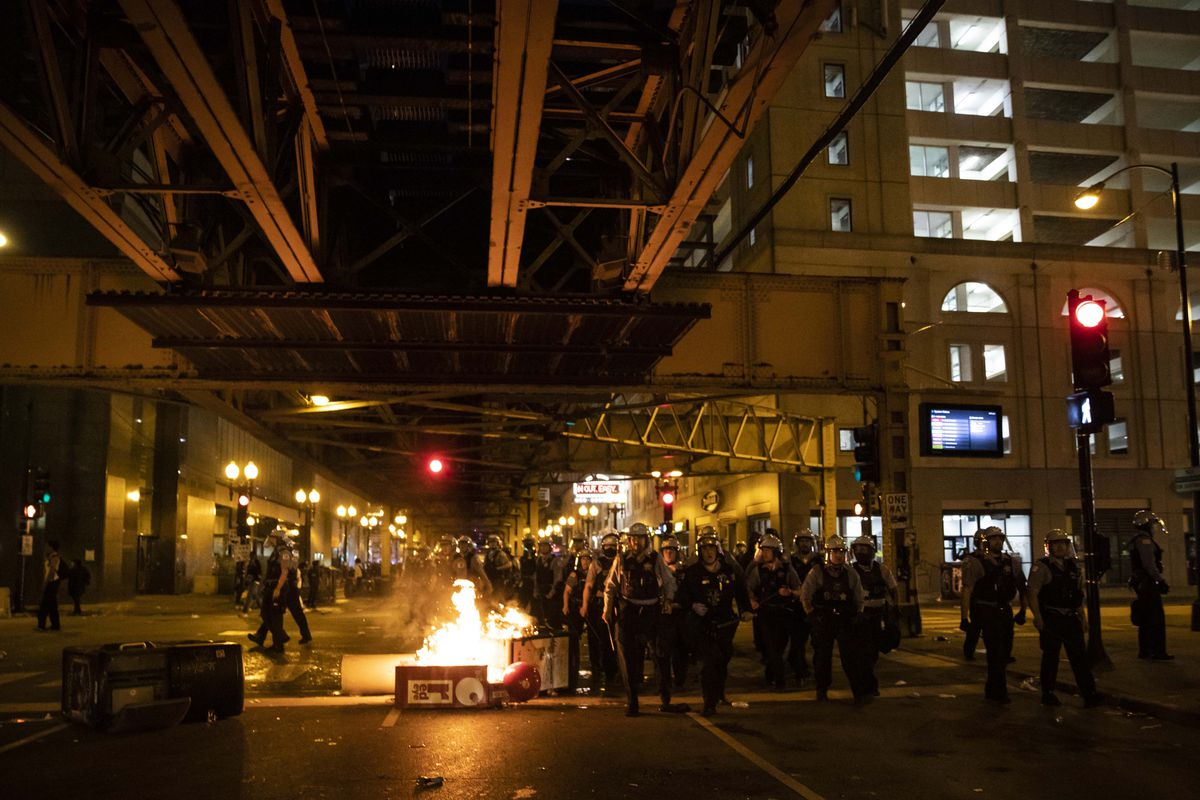 Chicago police officers walk past a garbage can that was set on fire on Lake Street in the Loop as thousands of protesters in Chicago joined national outrage over the killing of George Floyd in Minneapolis police custody, Saturday afternoon, May 30, 2020.