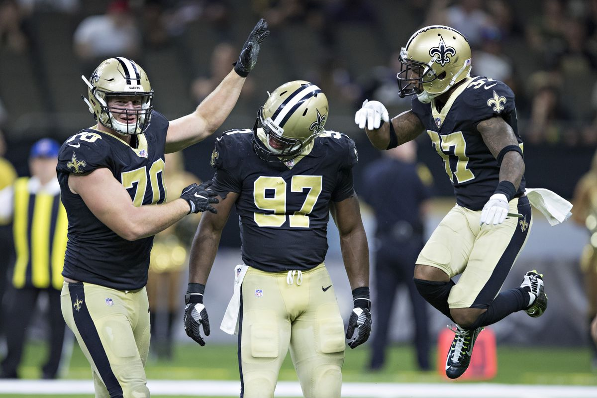 NEW ORLEANS, LA - Al-Quadin Muhammad (97) of the New Orleans  Saints celebrates with teammates Mitchell Loewen (70) and Arthur Maulet  (37) after sacking the quarterback during a preseason game against the  Baltimore Ravens at Mercedes-Benz Superdome