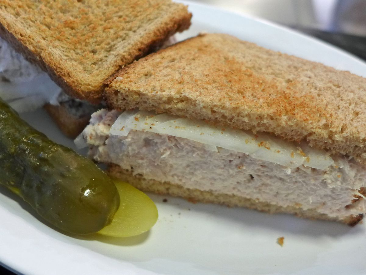 Eisenberg's tuna salad sandwich has lots of thick tuna piled onto wheat bread. There's a pickle on the side.