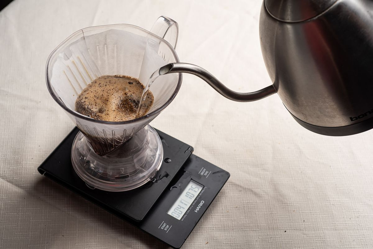 Clever Coffee Dripper sits on top of a scale, water is being poured into the top, where coffee grounds are.