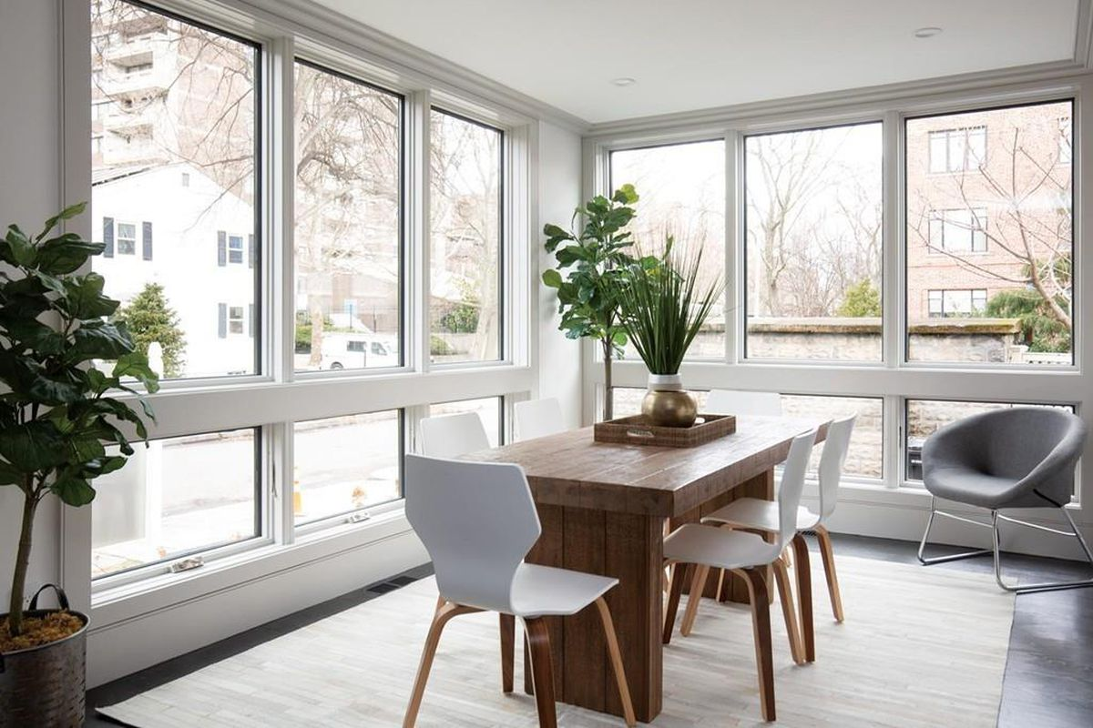 A dining room with a table and chairs next to floor-to-ceiling windows that meet at a corner.