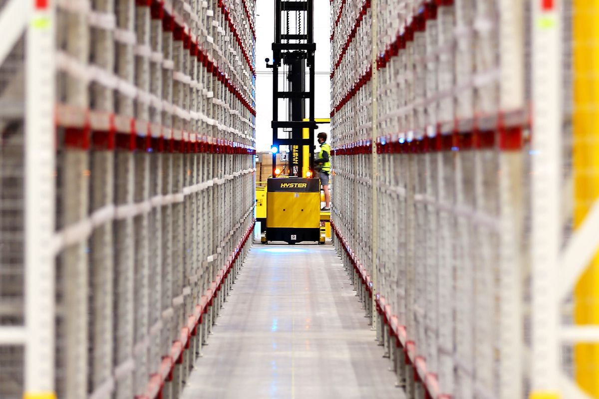 A worker retrieves an item from high up on one of the numerous aisles inside the newly opened Amazon fulfillment center in South Jordan on Monday, Sept. 14, 2020.