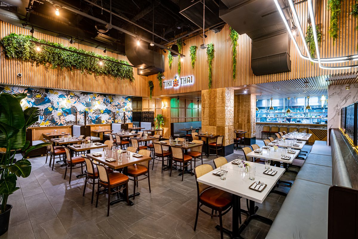 Tiki Thai's dining room is full of wood paneling, lights, and greenery