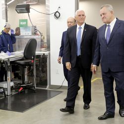 Vice President Mike Pence, center, tours a clean room with Merit Medical founder, chairman and CEO Fred Lampropoulos, right, and Secretary of Commerce Wilbur Ross, left, in the Rex and Anita Bean Building at Merit Medical headquarters in South Jordan on Thursday, Aug. 22, 2019.