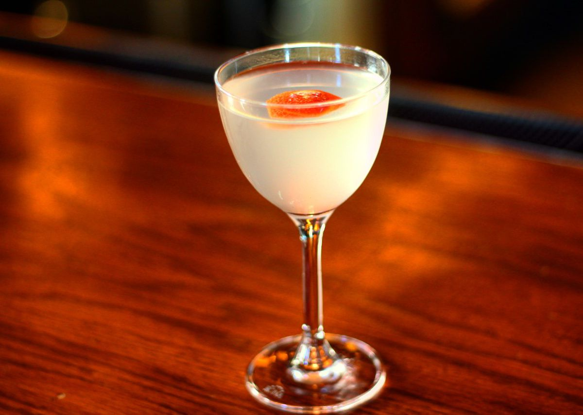 A pale yellow martini in a small glass sits on a dark wood bar