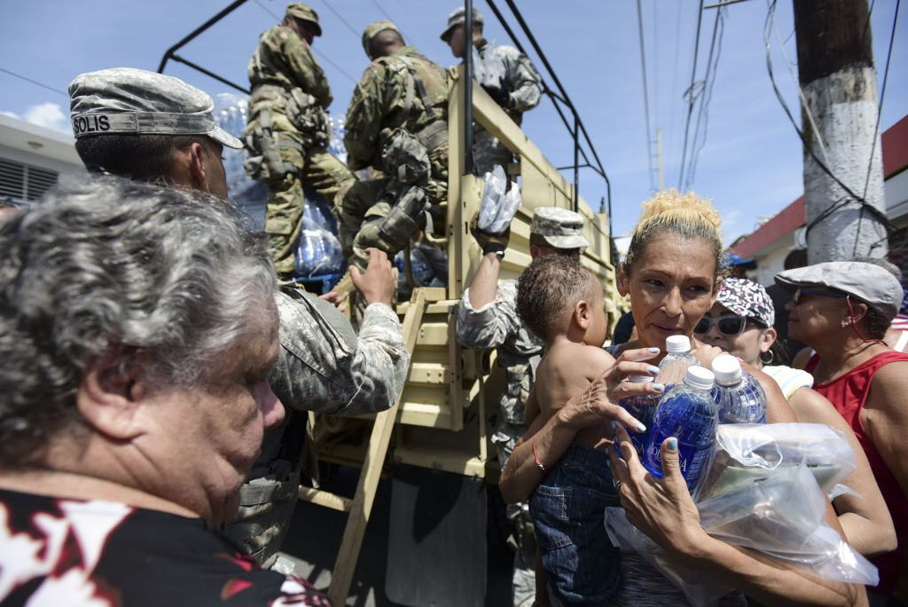 National Guard Soldiers arrive at Barrio Obrero in Santurce on Sept. 24, 2017, to distribute water and food among those affected by the passage of Hurricane Maria, in San Juan, Puerto Rico. Federal aid is racing to stem a growing humanitarian crisis in to