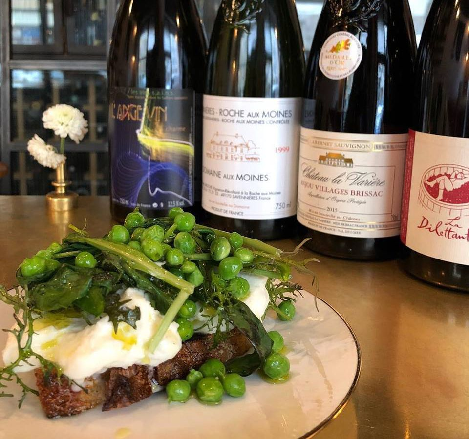 An open-faced sandwich with mozzarella, peas and greens in front of several wine bottles