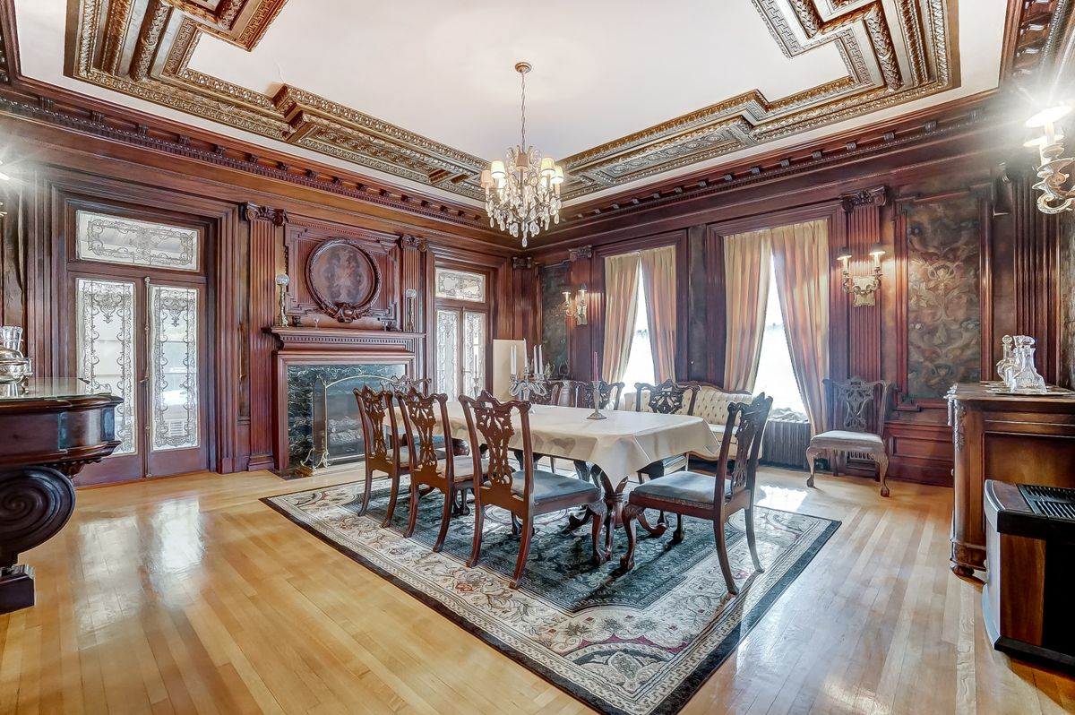 A dining room has a chandelier, crown molding, woodworking, and wood floors.