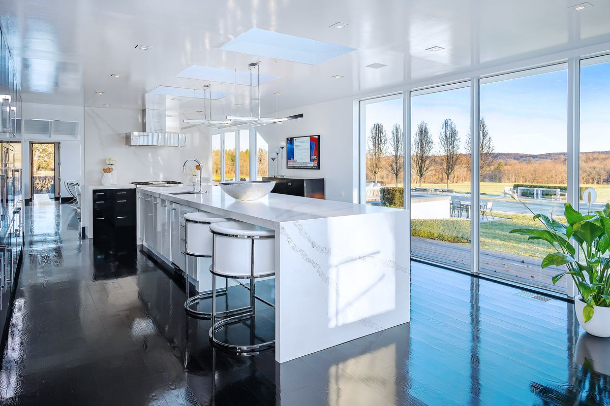 A white island in the kitchen contrasts with glossy black floors. Large windows look onto a covered pool.
